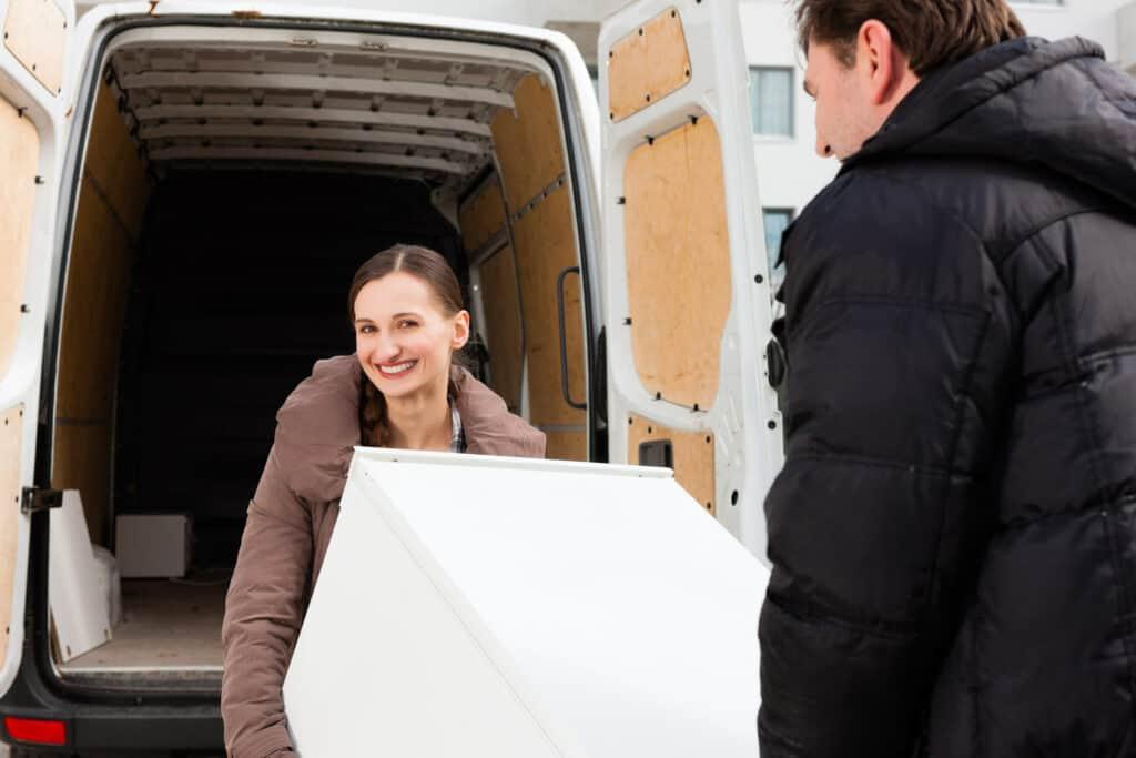 Frau und Mann transportieren Kühlschrank